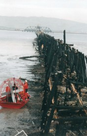 A fan boat tries to edge nearer to the severely burned rail bridge.