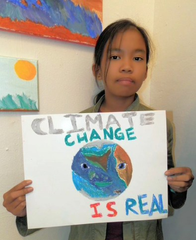 Hayward resident Quin Llamido, age 10, says she is very concerned about climate change and attended a sign-making workshop at Hayward's Sun Gallery over the weekend for the city's upcoming March for Science on the Hayward Shoreline.