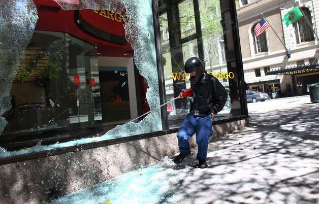 A black-clad protester breaks a window at a Wells Fargo branch during a May Day rally on Tuesday, May 1, 2012 in downtown Seattle. Photo: JOSHUA TRUJILLO / SEATTLEPI.COM