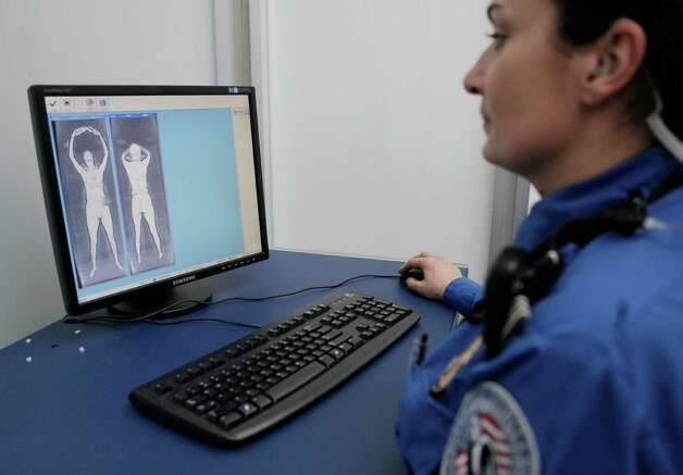 A Transportation Security Administration officer checks body scans on a computer screen as volunteers go through the first full body scanner installed at O'Hare International Airport , Monday, March 15, 2010, in Chicago. Federal transportation authorities demonstrated the technology to the media before starting to send passengers through the machine later today. Officials say they don't expect the body scanner which takes seconds to pass through to slow down security lines. (AP Photo/M. Spencer Green) Photo: M. Spencer Green, ASSOCIATED PRESS / ASSOCIATED PRESS