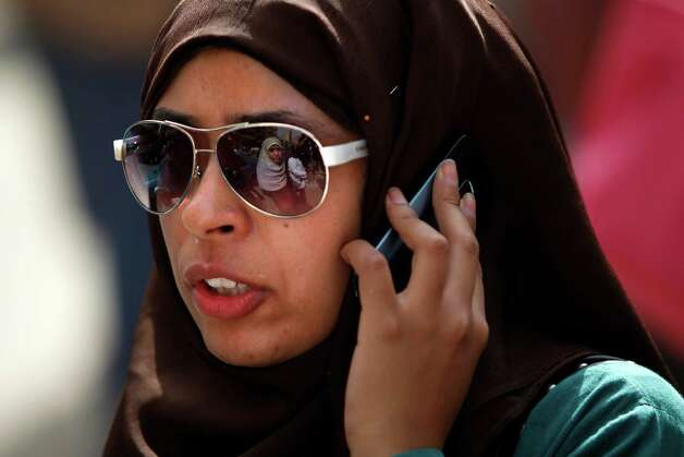 An Egyptian woman talks on her mobile phone as she waits to vote at Ibn Nafis Language school polling station in Nasr City, Cairo, Egypt, Wednesday.(AP Photo/Fredrik Persson) Photo: Fredrik Persson, Associated Press / AP
