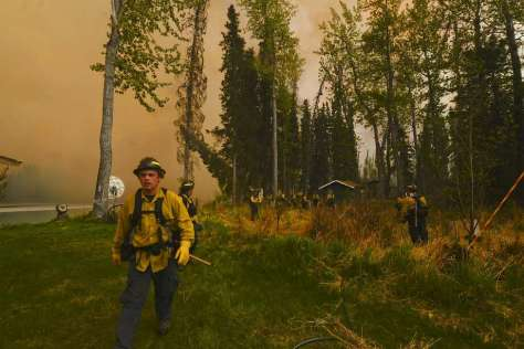 Firefighters assess whether they can protect a property during a 2014 wildfire in Soldotna, Alaska. south of Anchorage. Photo: Rashah McChesney, Associated Press