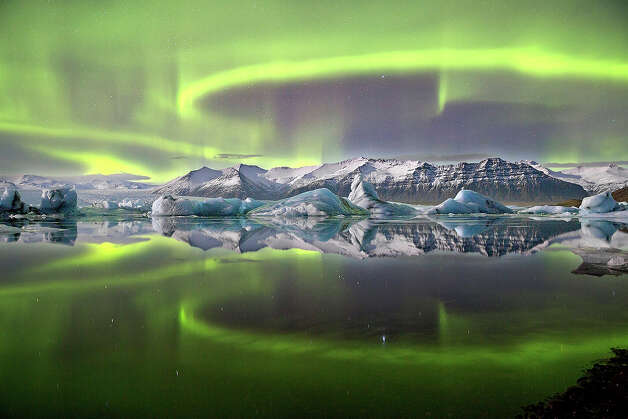Aurora over a Glacier Lagoon byJames Woodend (UK)*A vivid green overhead aurora pictured in Iceland's Vatnajškull National Park reflected almost symmetrically in Jökulsárlón  Glacier lagoon. A complete lack of wind and current combine in this sheltered lagoon scene to create an arresting mirror effect, giving the image a sensation of utter stillness. Despite this, there is motion on a surprising scale, as the loops and arcs of the aurora are shaped by the shifting forces of the EarthÕs magnetic field.*Overall winner Photo: Contributed Photo / Connecticut Post Contributed
