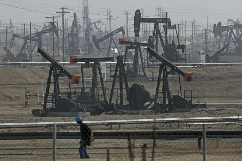 A person walks past pump jacks operating at the Kern River Oil Field in Bakersfield, Calif. (AP Photo/Jae C. Hong, File) Photo: Jae C. Hong, Associated Press
