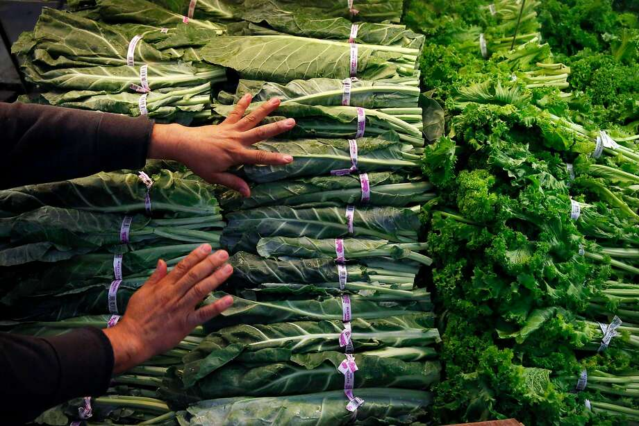 Produce manager Rafael Cisneros restocks greens at the store, which has about 2,200 customers daily. Photo: Leah Millis, The Chronicle