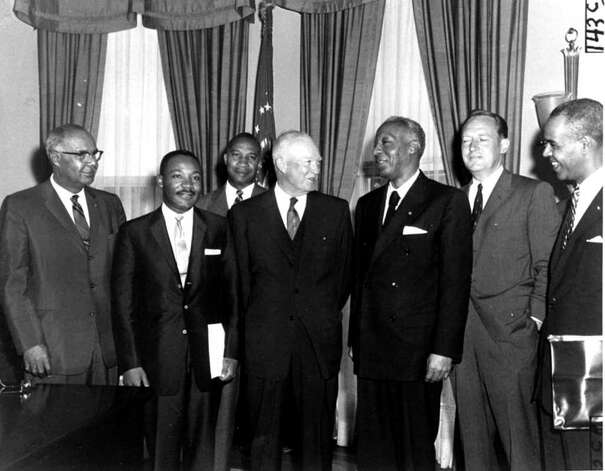 """President Eisenhower poses in his office, June 23, 1958, with black leaders with whom he discussed civil rights issues.  Left to right:  Lester B. Granger, executive secretary, National Urban League; Dr. Martin Luther King, Jr., Montgomery, Al., president of the Southern Leadership Conference; E. Frederic Morrow, White House administrative officer; Eisenhower; A. Philip Randolph, AFL-CIO vice president and head of International Brotherhood of Sleeping Car Porters; Attorney General William Rogers; and Roy Wilkins, executive secretary of the National Association for the Advancement of Colored People.  The callers told Eisenhower that court ordered suspension of school integration at Little Rock, AR  """"has shocked and outraged black citizens and millions of their fellow Americans.""""  (AP Photo) / Beaumont"""