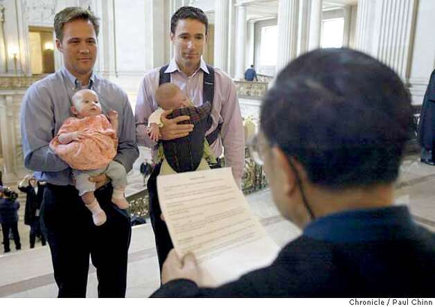 Holding the twin daughters Sophia and Elizabeth, Eric Etherington (left) exchanges marriage vows with Doug Okun