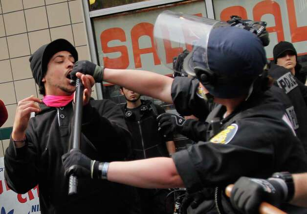 A man gets  punched in the face by police for pushing an officer during a May Day rally on Tuesday, May 1, 2012 in downtown Seattle. Photo: JOE DYER / SEATTLEPI.COM