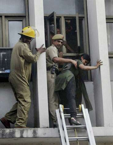 Fire personnel rescue a woman after a fire broke out in a multi-story building housing the Punjab National Bank at Parliament Street in New Delhi, India, Wednesday. No casualty has been reported. Some of the injured, who had trouble in breathing, have been taken to hospitals, according to local news reports. (A Photo) INDIA OUT Photo: Associated Press / SL