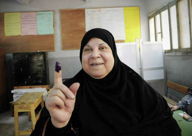 An Egyptian woman shows her inked finger after casting her vote inside a polling station, in Giza, Egypt, Wednesday. More than 15 months after autocratic leader Hosni Mubarak's ouster, Egyptians streamed to polling stations Wednesday to freely choose a president for the first time in generations. (AP Photo/Mohammed Asad) Photo: Mohammed Asad, Associated Press / AP