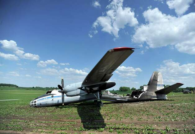 An AN-30 military aircraft lies off the runway at the Czech air force base in Caslav, some 20 miles east of Prague, Wednesday. An official says the Russian military plane caught fire after problems during the landing maneuver, injuring at least six people on board. Czech military spokeswoman Jana Ruzickova said the plane had 23 people on board, 14 Russians and nine Czechs. Five Russians and one Czech national have suffered injuries, mostly burns. The plane and Russian officials were in the Czech Republic on a regular monitoring mission. (AP Photo/CTK, Josef Vostarek) Photo: Josef Vostarek, Associated Press / CTK