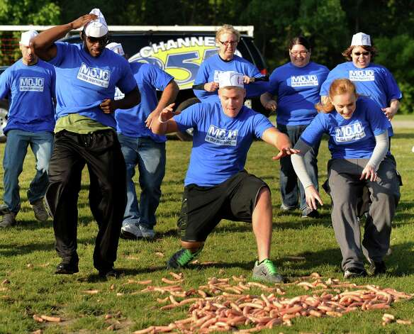Contestants scramble to pick up Coney hot dogs dropped from a helicopter at H.Y.P.E. Recreation Center field in Dearborn Heights on Wednesday in Dearborn Heights, Mich. Contestants will have 95 seconds to gather as many as they can. The dogs will then be donated to a local dog rescue charity for food. (AP Photo/Detroit News, David Coates) Photo: Associated Press / SL