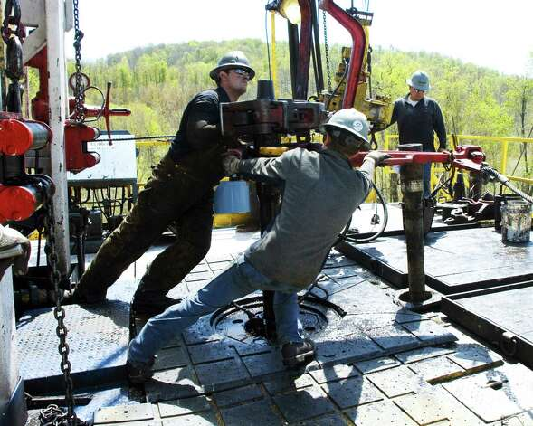 Workers move a section of well casing into place at a Chesapeake Energy natural gas well site near Burlington, Pa. Natural gas is abundant and cheap these days. (AP Photo/Ralph Wilson, file) Photo: Ralph Wilson