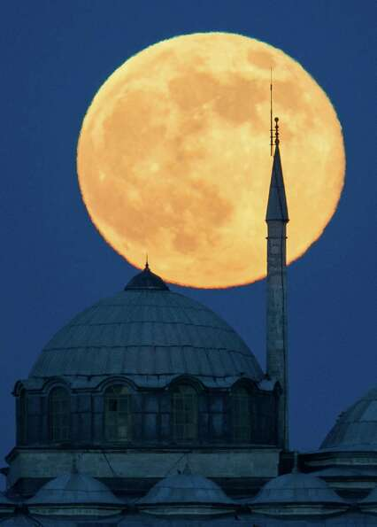 The supermoon rises behind a building of the Topkapi Palace in Istanbul, Turkey. The moon, which wil