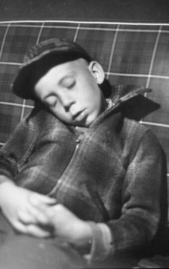 Exhausted Mike Gipson sleeping in car after 1949 coon hunt.