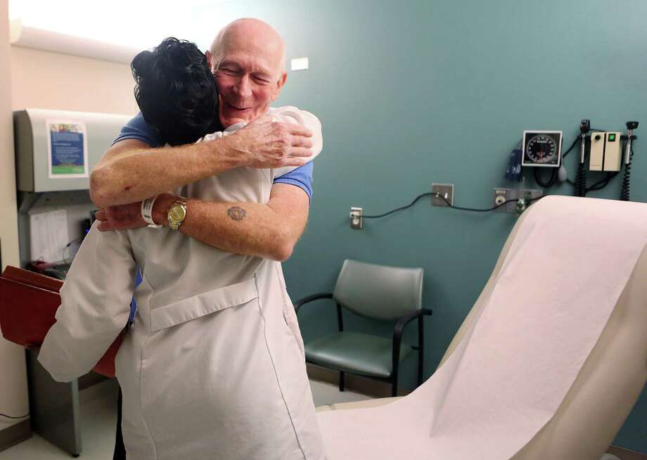 Nurse Beena Varghese greets Bruce Campbell during his appointment at MD Anderson Cancer Center last month. Campbell, who has Stage 4 lung cancer, has been receiving immunotherapy for the last year and a half.  His oncologist, John Heymach, below, proposed the treatment. Photo: Mayra Beltran, Staff / © 2015 Houston Chronicle