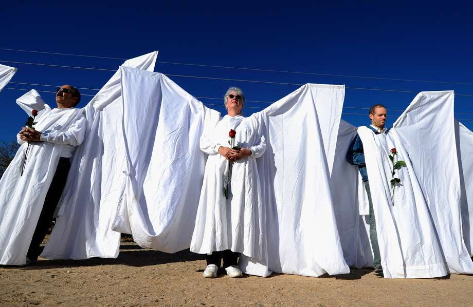 """A group of staff and volunteers from Orlando Shakespeare Theater as well as the Orlando arts community work together to build """"Angel Wings"""" to block Westboro Baptist Church members protesting the funerals of the Orlando shooting victims. When finished, they will look like this.Pictured: Mourners dressed as angels stand across the street from St. Elizabeth Ann Seton church where the funeral service for US District Court Judge John Roll is being held on January 14, 2011 in Tucson, Arizona."""