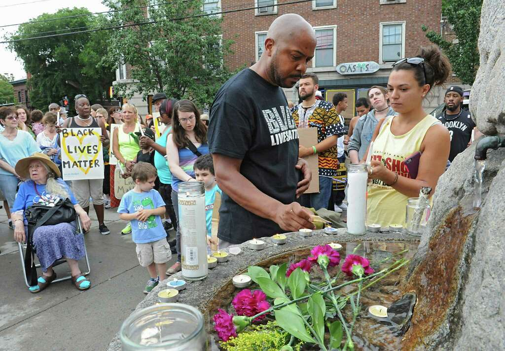 Truemaster Trimingham of Albany, left, and Melissa Fleck of Albany light candles as people gather in Dana Park to mourn the lives of five black and brown men killed by police this week on Friday, July 8, 2016 in Albany, N.Y. Also honored was the life of Goddess Diamond, the 14th Black trans woman killed this year. (Lori Van Buren / Times Union) Photo: Lori Van Buren / 20037276A
