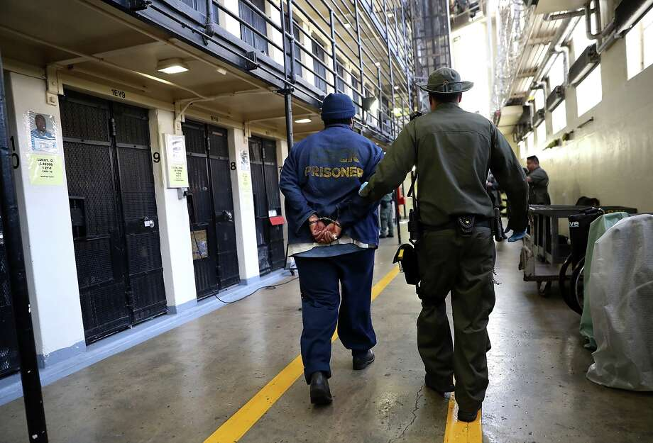 An armed California Department of Corrections and Rehabilitation (CDCR) officer escorts a condemned inmate at San Quentin State Prison. Photo: Justin Sullivan/Getty Images