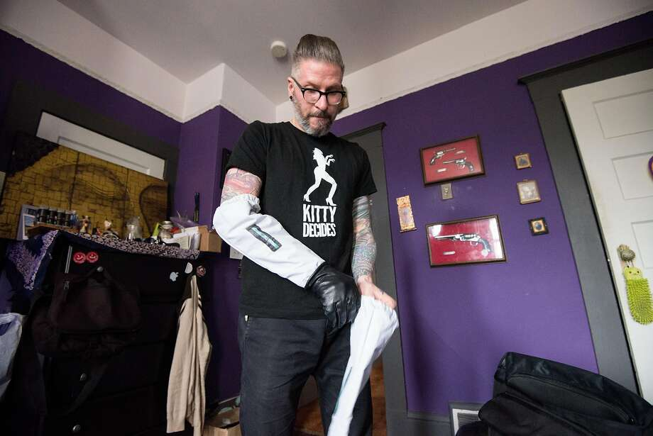 "Daniel ""DQ"" Quagliozzi, top, shows the padded sleeves that help him handle troubled cats while his kitty, Cubby, above, rests comfortably in his cushioned bed in their San Francisco apartment. Photo: Max Bouvatte, Special To The Chronicle"
