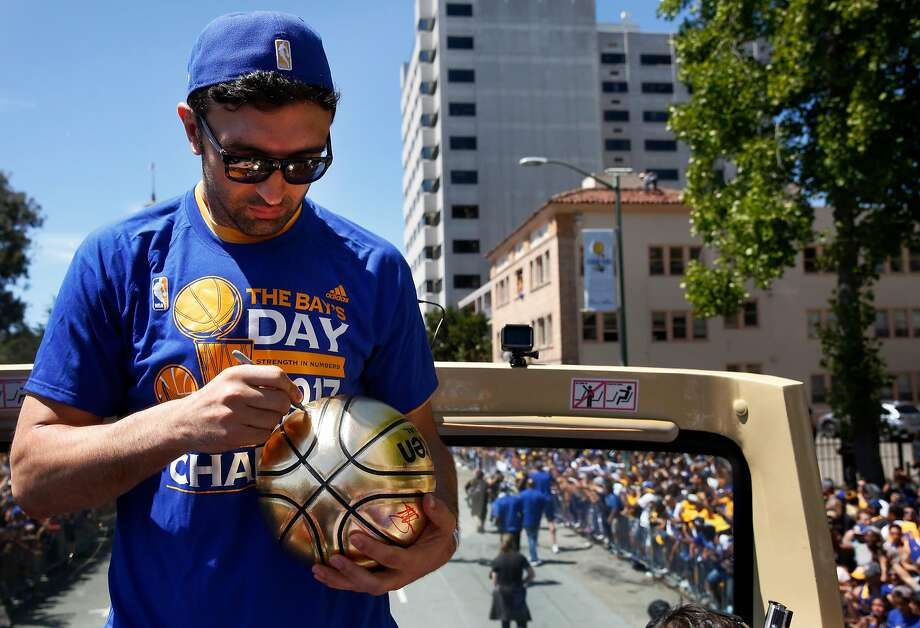 FILE – Zaza Pachulia signs a ball thrown to him from a fan during the Warriors' 2017 NBA Championship parade in Oakland in this file photo from June 15, 2017. Photo: Leah Millis, The Chronicle