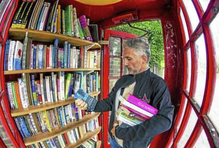 A visitor browses books in an honor library inside a converted red telephone box on Lewisham Way in London. Photo: Miles Willis — Bloomberg Photo / Bloomberg