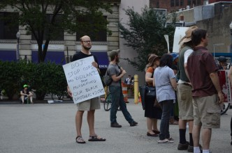 """A mostly white-appearing group stands at the back of a crowd in downtown Pittsburgh. Some bushes, trees, and a building with purple awnings are visible in the background. A few people hold signs facing right, probably towards a speaker. A white-appearing person with a short beard and glasses faces the camera with a sign held to their chest. The sign is white with black marker writing, and it reads: """"DOJ: STOP COPS AND VIGILANTES FROM MURDERING OUR BLACK BROTHERS & SISTERS."""""""