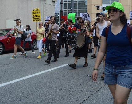 "A multiracial (but predominantly white-appearing) group of marchers walk down a downtown Pittsburgh street. Many of them have instruments -- including a drum, saxophone, and trumpet. Some people carry signs, including a yellow sign with black printed writing that reads, ""Stop Racist Police Terror."" A white-appearing person with a blue tee shirt, sunglasses, and shoulder-length hair is in the right corner, towards the front of the group. They wear a neon green hat that says ""National Lawyers Guild Observer."""