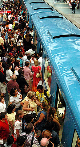 People surging into cars in a transit station
