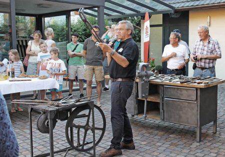 Josef Gruseck (Mitte) zeigt beim historischen Rundgang in Allmannsweier anlässlich des Dorfjubiläums den Teilnehmern alte Schmiedewerkzeuge. Foto:© Beate Rottler