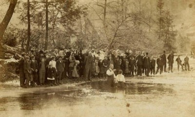 Black and white photo of a group of around fifty people stand along the riverbank, watching a baptism happening within its waters.
