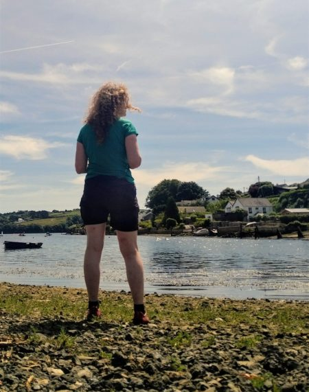 The Beginner Hikers Guide to Hiking and Walking Gear. Walker in shorts and tee-shirt standing on a beach on a creek in Cornwall, UK.