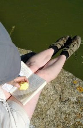 6 Books For Walkers. Woman sat on the edge of a quay reading.