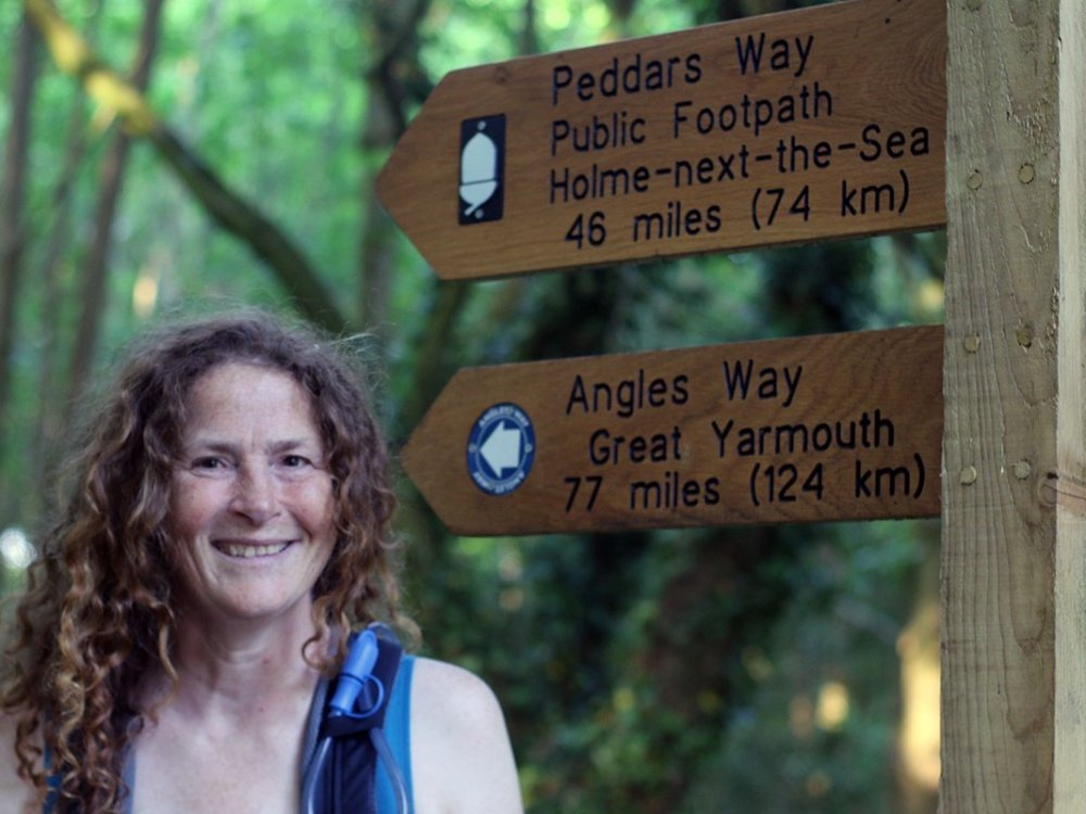Stephanie Boon standing beside the Peddars Way National Trail sign, Peddars Way, Norfolk UK. Copyright Linda Barlow, 2018.