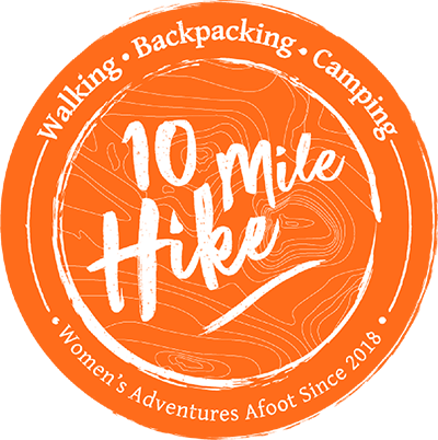 10 Mile Hike logo. Circular. Orange background, white text: 10 Mile Hike, Walking, Backpacking, Camping,Women's Adventures Afoot Since 2018