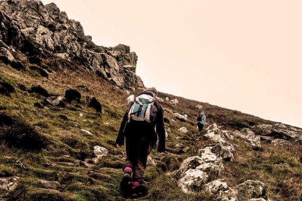 2 women out for an adventure, climbing the rocky cliffs near Zennor, Cornwall, UK.