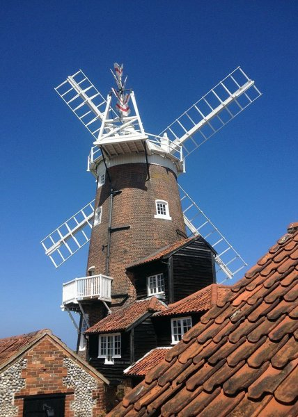 Close view of a windmill across red pantile roofs. Norfolk Coast Path, 2018