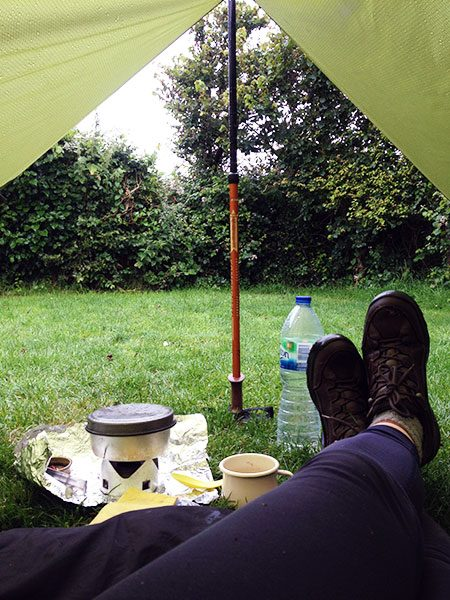 Budget Backpacking: View from a tarp that show feet and a cooking stove with a view of a campsite hedge! Bude, 2017.