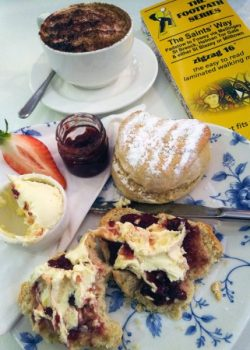 Cream tea with 2 scones, jam, cream and a cappuccino, beside a yellow Saints Way map
