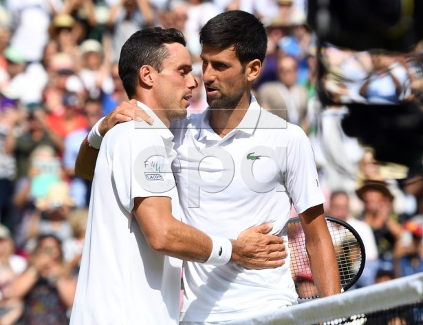 Novak Djokovic of Serbia (R) at the net with Roberto Bautista Agut of Spain whom he defeated in their semi final match during the Wimbledon Championships at the All England Lawn Tennis Club, in London, Britain, 12 July 2019. EPA-EFE/ANDY RAIN EDITORIAL USE ONLY/NO COMMERCIAL SALES