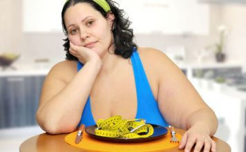 Curvy lady sitting at table with nothing to eat