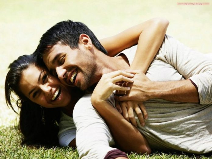 Couple playing around, laying down on ground, holding each other