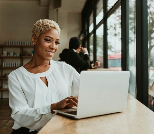 11 legit ways to make money online Happy businesswoman in a cafe using her laptop