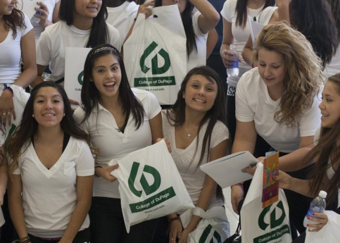 best universities - Group of Hispanic girls with green and white bags at college