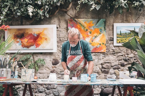Photo by Eddy Klaus Man in striped apron paints canvases in Bardolino