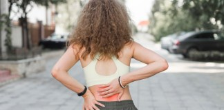 7 Things To Know Before Using CBD Oil For Pain rear-view-of-woman-standing-on-street-having-backache_23-2147889594
