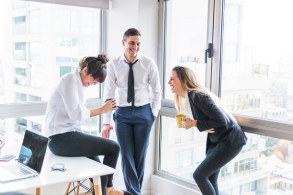 businessman-looking-two-businesswoman-laughing-office_23-2147857267