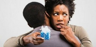 10 Physical Signs He's Cheating confused woman holding present behind man's back while hugging him