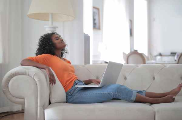 STD screening dark skinned woman sitting on white sofa by Andrea Piacquadio