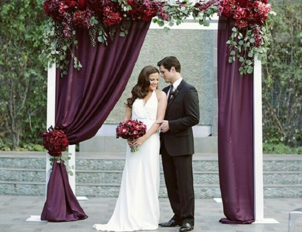 wedding altar with burgundy drapes decorated with beautiful seasonal flowers
